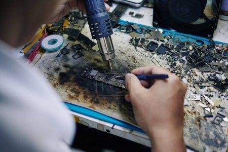 Photo for Technician using hot air gun when repairing logic board at his desk - Royalty Free Image