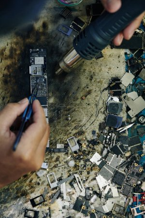 Photo for Hands of technician using professional hot air gun when fixing logic board, view from above - Royalty Free Image