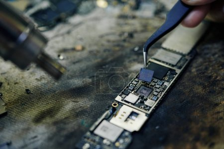 Photo for Repairman taking small parts of logic board with tweezers when fixing problem - Royalty Free Image