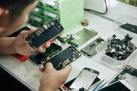 Photo for Close-up image of repairman examining smartphones before fixing them - Royalty Free Image