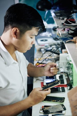 Photo for Young Asian repairman opening small drawer when searching for details for broken smartphone - Royalty Free Image