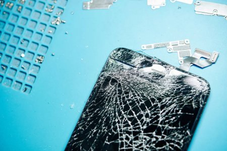 Photo for Close-up image of smashed smartphone screen on desk of repairman, view from above - Royalty Free Image