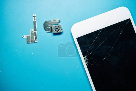 Photo for Smartphone screen with long cracks with removed bracket and camera on desk with blue surface, view from above - Royalty Free Image