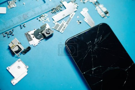 Photo for Cracked modern smartphone, broken camera, metal brackets and screws, view from above - Royalty Free Image