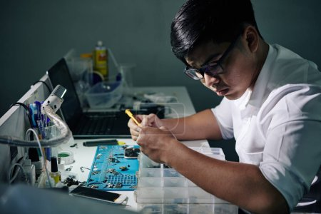 Photo for Serious Vietnamese repairman in glasses searching for smartphone details in plastic box - Royalty Free Image