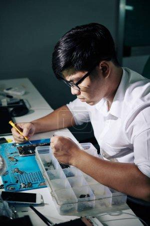 Profesjonalny wietnamski mechanik skoncentrowany na naprawianiu smartfonów