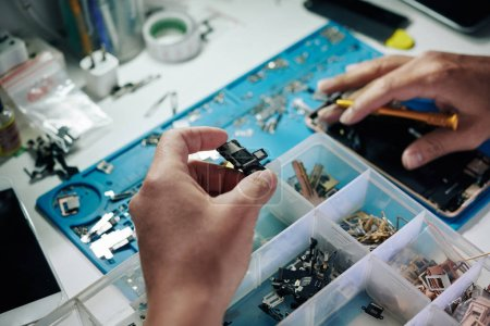 Photo for Tablet computer logic board in hand of repairman searching for same detail in plastic box - Royalty Free Image