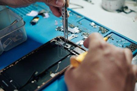 Photo for Hands of repairman using tweezers when fixing smartphone camera - Royalty Free Image