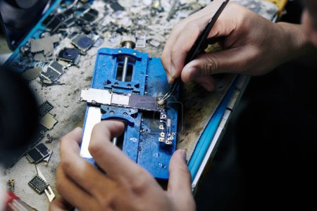 Photo for Repairman using tweezers for applying or removing solder paste on logic board of smartphone - Royalty Free Image