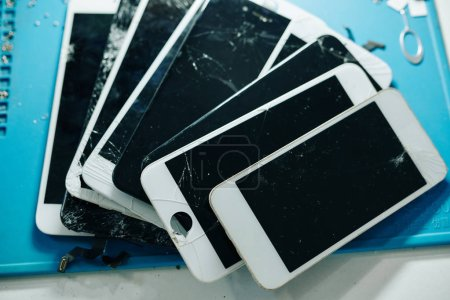 Photo for Cracked or broken removed smartphone screens on table of repairman, view from above - Royalty Free Image