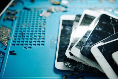 Photo for Smashed and cracked smartphone screens on table in repair workshop, selective focus - Royalty Free Image