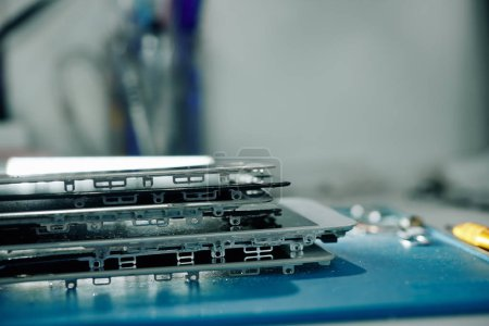 Photo for Stack of removed smartphone screens in workshop of repairman - Royalty Free Image