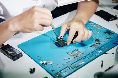 Photo for Hands of repairman removing back panel of smartwatch when fixing it - Royalty Free Image