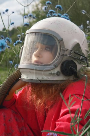 close-up portrait of pretty young woman in space helmet outdoor with blue wild flowers
