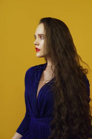 close-up portrait of young sensual brunette woman with curly long hair in blue dress on yellow background