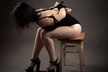 tied rope brunette sitting on chair, concept bdsm