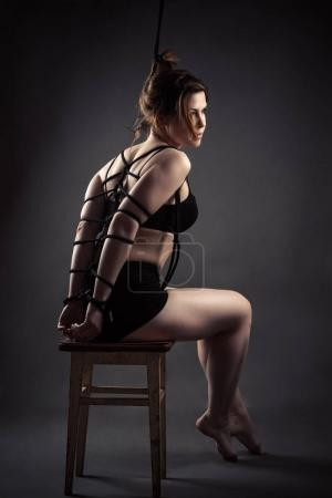 beautiful sexy female slave sitting bondage ropes on chair
