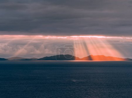 Photo for Sunset over the Outer Hebrides, as seen from the Neist Point cliff on the Isle of Skye, Scotland. Dramatic rays of light beaming through the dark clouds and shine in the deep blue sea on a summer day. - Royalty Free Image