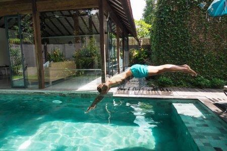 Photo pour Vue latérale de l'homme tatoué plongeant dans la piscine pendant les vacances sur bali, indonésie - image libre de droit