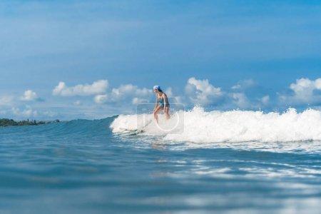 Photo pour Vue latérale de la femme en maillot de bain surf dans l'océan - image libre de droit