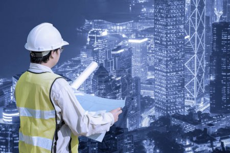Construction engineer checking construction drawing with modern cityscape
