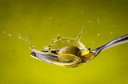 Photo pour Croquis avec des gouttelettes obtenues à partir d'une olive qui tombe sur une cuillère pleine d'huile d'olive - image libre de droit