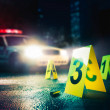 Police car at a crime scene with evidence markers,...