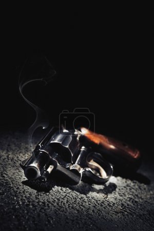 gun with smoke on the floor, high contrast image