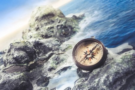 vintage compass on the sea shore