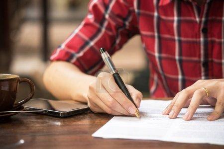 Photo pour La main de l'homme va écrire quelque chose sur la page du carnet vierge sur la table de bureau en bois . - image libre de droit