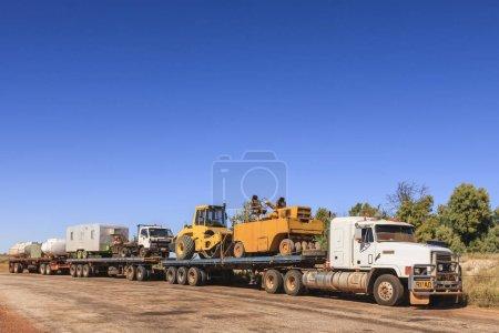 Photo pour Train routier dans l'arrière-pays du Territoire du Nord, en Australie, dans une aire de repos, transportant du matériel de construction routière. Rouleau de route, caravane, camion, réservoirs d'eau et de carburant et plus . - image libre de droit