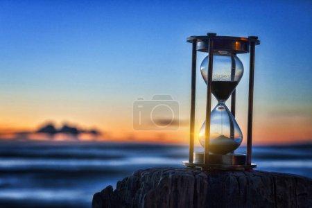 Photo pour Sablier ou sablier devant un beau clair lever ou un coucher de soleil. - image libre de droit