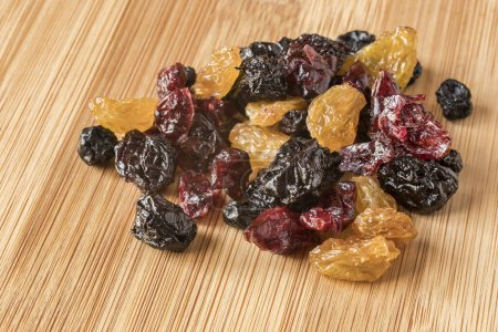 Photo for A handful of mixed dried fruit, with golden raisins, cherries, blueberries and cranberries, on a bamboo board. - Royalty Free Image