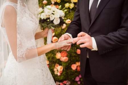 close-up of male and female hands with rings at beautiful wedding day