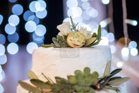close-up of delicious wedding cake with flowers and green leaves for celebration