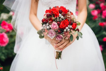 close-up of female hands holding beautiful wedding bouquet of colored flowers