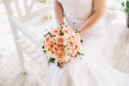Bride on white dress holding elegant wedding bouquet with orange tiny roses