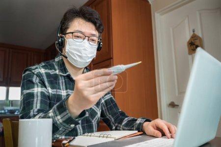 Photo pour Un Asiatique qui est isolé et qui travaille à la maison à cause d'une pandémie massive. Un homme tenant un thermomètre pour mesurer la température corporelle . - image libre de droit