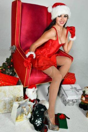 Photo pour Brune sexy habillée en Mme Père Noël posant jolie assise dans un fauteuil classique. Décoration de Noël . - image libre de droit