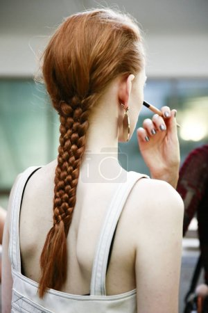 MILAN, ITALY - SEPTEMBER 23: A model is getting ready backstage ahead of the Jil Sander show during Milan Fashion Week Spring/Summer 2018 on September 23, 2017 in Milan, Italy.