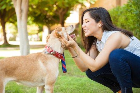 Photo pour Vue du profil d'une belle jeune femme tenant son chien face à face et sur le point de lui donner un baiser - image libre de droit