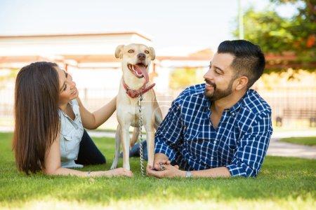 Photo pour Beau couple de propriétaires de chiens se relaxant dans un parc par une journée ensoleillée avec leur ami amical - image libre de droit