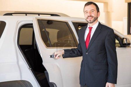 Photo pour Portrait d'un beau et professionnel conducteur ouvrant la porte de la voiture - image libre de droit