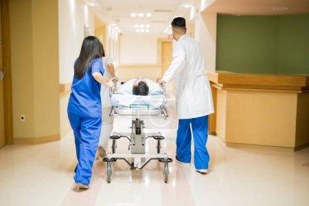 Photo pour Vue arrière pleine longueur d'un groupe de médecins transportant un patient dans une civière à l'hôpital - image libre de droit
