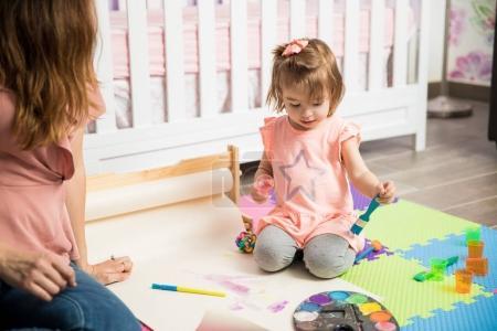 Photo pour Maman latine Sweet passer du temps avec son enfant mignon Peinture sur le plancher de la chambre à coucher - image libre de droit