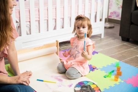 Child painting on bedroom floor