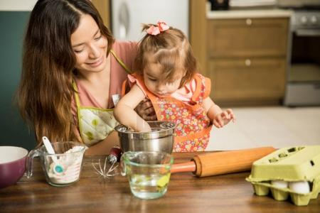 Girl helping mother prepare cake