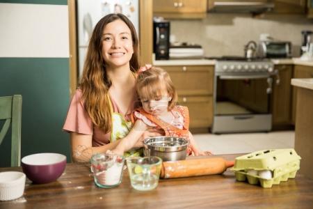 Photo pour Fille de peu deux ans aidant sa douce maman préparer gâteau à la cuisine domestique - image libre de droit