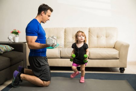 Girl exercising with father