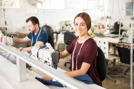 Photo for Portrait of a beautiful young Hispanic woman working as a tailor in a textile factory and smiling - Royalty Free Image